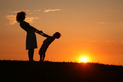 mother-son-sunset-holding-hands-7092227